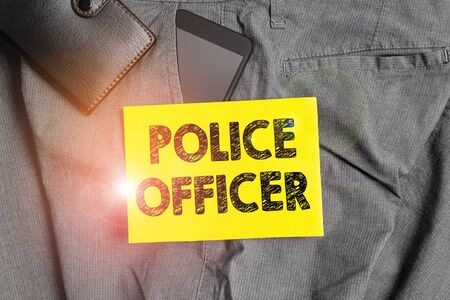 Word writing text Police Officer. Business photo showcasing a demonstrating who is an officer of the law enforcement team Smartphone device inside trousers front pocket with wallet and note paper 版權商用圖片