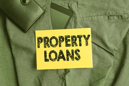 Word writing text Property Loans. Business photo showcasing a loan used to buy land or buildings and infrastructures Smartphone device inside trousers front pocket with wallet and note paper Banque d'images