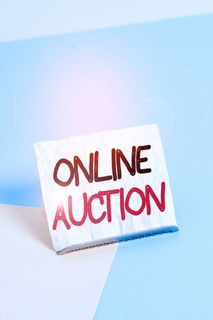 Writing note showing Online Auction. Business concept for process of buying and selling goods or services online Paper on buffer wire on soft pastel multi colours backdrop
