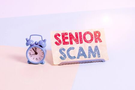 Writing note showing Senior Scam. Business concept for fraud schemes targeting the lifestyle and savings of the elderly Alarm clock beside a Paper sheet placed on pastel backdrop