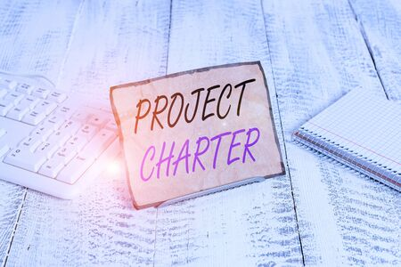 Text sign showing Project Charter. Business photo showcasing typically short formal document that describes your project Notepaper stand on buffer wire in between computer keyboard and math sheets