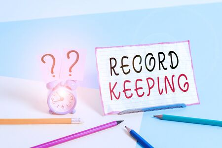 Text sign showing Record Keeping. Business photo showcasing The activity or occupation of keeping records or accounts Mini size alarm clock beside stationary placed tilted on pastel backdrop