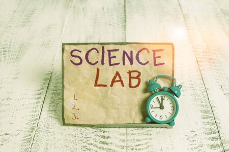 Word writing text Science Lab. Business photo showcasing special facility where experiments are done and with equipment Mini blue alarm clock stand tilted above buffer wire in front of notepaper