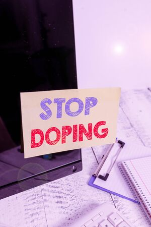 Text sign showing Stop Doping. Business photo text do not use use banned athletic perforanalysisce enhancing drugs Note paper taped to black computer screen near keyboard and stationary 版權商用圖片