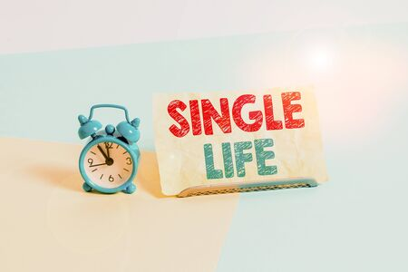 Writing note showing Single Life. Business concept for not vowed to someone or something else Umarried demonstrating Alarm clock beside a Paper sheet placed on pastel backdrop