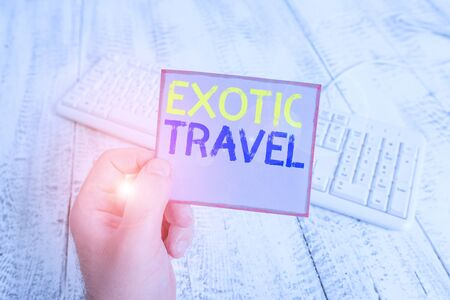 Word writing text Exotic Travel. Business photo showcasing Travelling to unusual places or unfamiliar destination man holding colorful reminder square shaped paper white keyboard wood floor 免版税图像