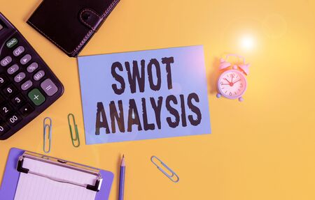 Text sign showing Swot Analysis. Business photo showcasing framework used to evaluate a company competitive position Clipboard clips sheet calculator pencil alarm clock wallet color background Imagens
