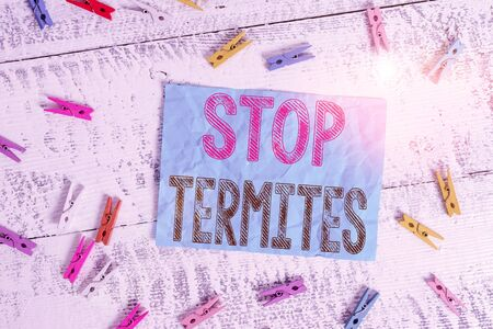 Writing note showing Stop Termites. Business concept for prevent a small tropical insect from damaging the woods Colored clothespin rectangle square shaped paper white wood background
