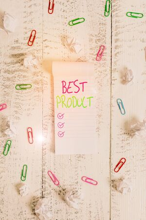 Conceptual hand writing showing Best Product. Concept meaning very popular and a large quantity of it has been sold Stripped ruled notepad clips paper balls wooden background
