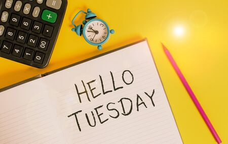 Writing note showing Hello Tuesday. Business concept for a greeting or warm welcome to the third day of the week Open striped notebook calculator metal alarm clock color background