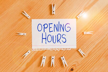 Conceptual hand writing showing Opening Hours. Concept meaning the time during which a business is open for customers Colored crumpled papers wooden floor background clothespin