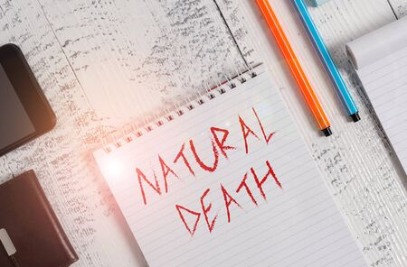 Text sign showing Natural Death. Business photo showcasing occurring in the course of nature and from natural causes Smartphone man wallet notebook pens ballpoints note pad old wooden table