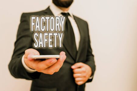 Handwriting text Factory Safety. Conceptual photo minimize risk of worker injury while doing production tasks Male human wear formal work suit hold smart hi tech smartphone use one hand