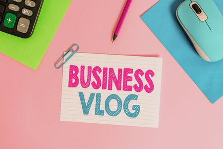 Writing note showing Business Vlog. Business concept for A video content about subject matter related to the company Electronic mouse calculator paper sheets clip marker colored background