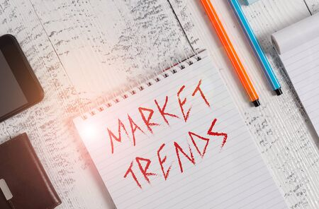 Text sign showing Market Trends. Business photo showcasing Changes and developments in buying and selling in the market Smartphone man wallet notebook pens ballpoints note pad old wooden table