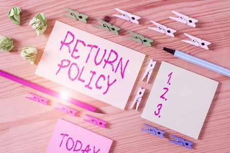 Writing note showing Return Policy. Business concept for return or exchange defective merchandise that they buy before Colored clothespin papers empty reminder wooden floor background office 免版税图像