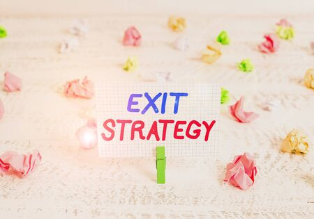 Conceptual hand writing showing Exit Strategy. Concept meaning Extricating oneself from a situation that is become difficult Green clothespin white wood background reminder office supply Banque d'images