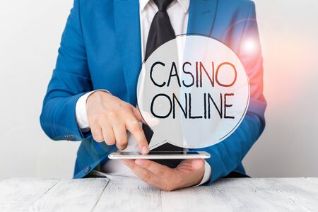 Handwriting text Casino Online. Conceptual photo gamblers can play and wager on casino games through online Businessman with pointing finger in front of him