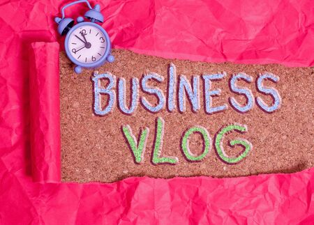 Text sign showing Business Vlog. Business photo showcasing A video content about subject matter related to the company Alarm clock and torn cardboard placed above a wooden classic table backdrop Banco de Imagens