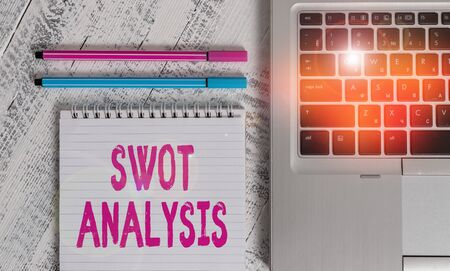 Writing note showing Swot Analysis. Business concept for framework used to evaluate a company competitive position Metallic laptop blank ruled notepad pens lying old wooden vintage table