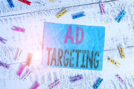 Writing note showing Ad Targeting. Business concept for target the most receptive audiences with certain traits Colored clothespin rectangle square shaped paper white wood background