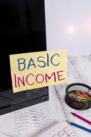 Text sign showing Basic Income. Business photo showcasing periodic cash payment unconditionally delivered Minimum income Note paper taped to black computer screen near keyboard and stationary