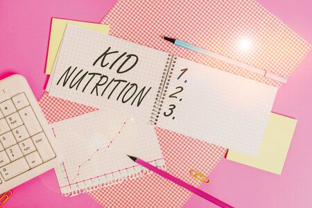 Conceptual hand writing showing Kid Nutrition. Concept meaning A healthy diet for children to help them grow and learn Writing equipments and computer stuff placed on plain table