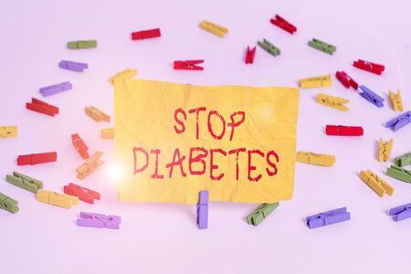 Word writing text Stop Diabetes. Business photo showcasing prevent the disease of elevating glucose level in the blood Colored clothespin papers empty reminder white floor background office