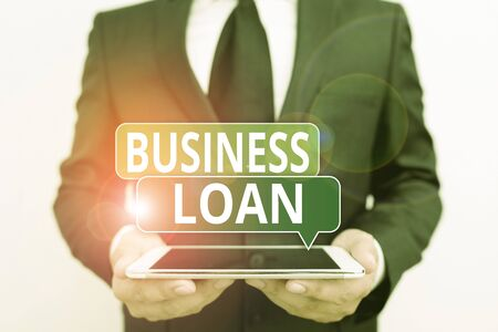 Conceptual hand writing showing Business Loan. Concept meaning Loans provided to small businesses for various purposes Male human wear formal work suit hold hitech smartphone