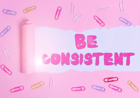 Word writing text Be Consistent. Business photo showcasing always behaving or happening in a similar positive way Paper clip and torn cardboard placed above a plain pastel table backdrop