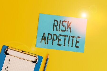 Conceptual hand writing showing Risk Appetite. Concept meaning the level of risk an organization is prepared to accept Clipboard holding paper sheet square page pen colored background Stock Photo