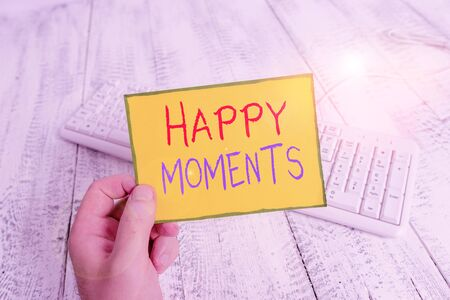 Handwriting text Happy Moments. Conceptual photo Feelings of pleasure or satisfaction with their life man holding colorful reminder square shaped paper white keyboard wood floor