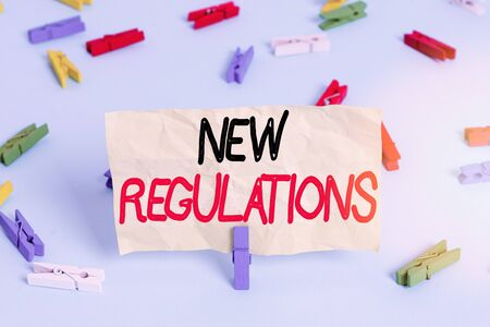 Text sign showing New Regulations. Business photo showcasing rules made government order control something done Colored clothespin papers empty reminder blue floor background office pin