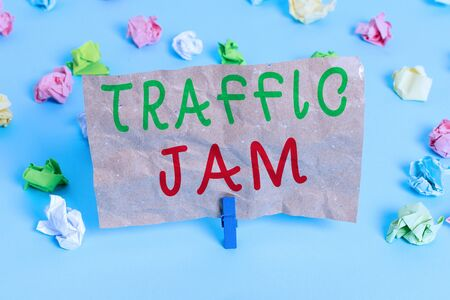 Text sign showing Traffic Jam. Business photo text a large number of vehicles close together and unable to move Colored crumpled papers empty reminder blue floor background clothespin Imagens