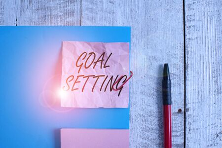 Text sign showing Goal Setting. Business photo showcasing process of identifying something that you want to accomplish Wrinkle paper and cardboard plus stationary placed above wooden background