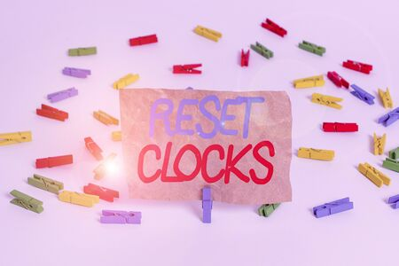Text sign showing Reset Clocks. Business photo text To revisit return to or recreate a time or era from the past Colored clothespin papers empty reminder white floor background office