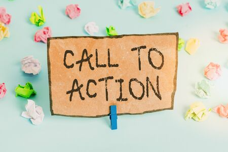 Handwriting text writing Call To Action. Conceptual photo exhortation do something in order achieve aim with problem Colored crumpled papers empty reminder blue floor background clothespin
