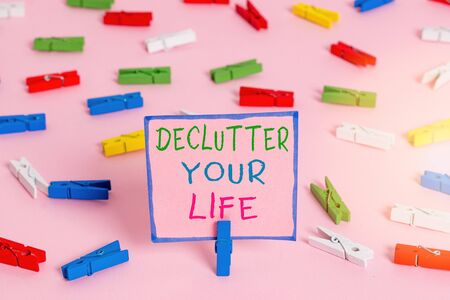 Word writing text Declutter Your Life. Business photo showcasing To eliminate extraneous things or information in life Colored clothespin papers empty reminder pink floor background office pin