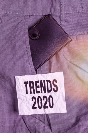 Text sign showing Trends 2020. Business photo showcasing general direction in which something is developing or changing Small little wallet inside man trousers front pocket near notation paper Standard-Bild - 142216267