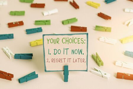 Word writing text Your Choices 1 Do It Now 2 Regret It Later. Business photo showcasing Think first before deciding Colored clothespin papers empty reminder pink floor background office pin