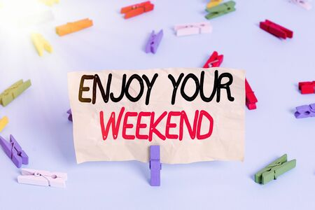 Text sign showing Enjoy Your Weekend. Business photo showcasing wishing someone that something nice will happen at holiday Colored clothespin papers empty reminder blue floor background office pin