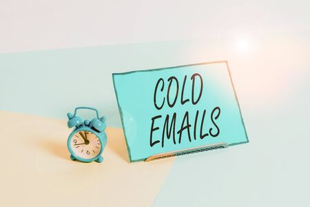 Conceptual hand writing showing Cold Emails. Concept meaning unsolicited email sent to a receiver without prior contact Alarm clock beside a Paper sheet placed on pastel backdrop