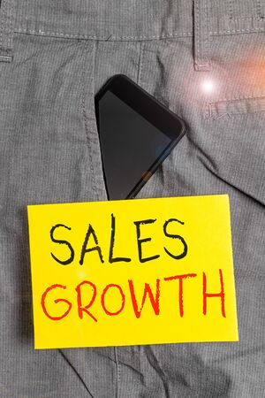 Word writing text Sales Growth. Business photo showcasing ability to increase revenue over a fixed period of time Smartphone device inside formal work trousers front pocket near note paper