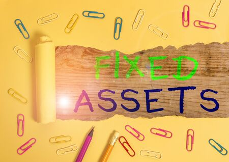 Writing note showing Fixed Assets. Business concept for longterm tangible piece of property or equipment a firm owns Stock Photo