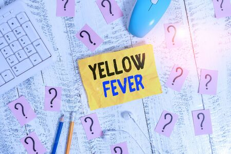 Conceptual hand writing showing Yellow Fever. Concept meaning tropical virus disease affecting the liver and kidneys Writing tools and scribbled paper on top of the wooden table Фото со стока