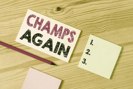 Text sign showing Champs Again. Business photo text refers to winner or someone who excels and enjoys victories Colored clothespin papers empty reminder wooden floor background office