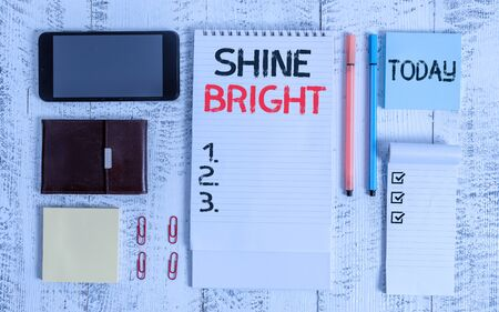 Word writing text Shine Bright. Business photo showcasing make an effort to live normally when in a difficult situation Smartphone wallet sticky notes clips notebook pens note pad wooden table