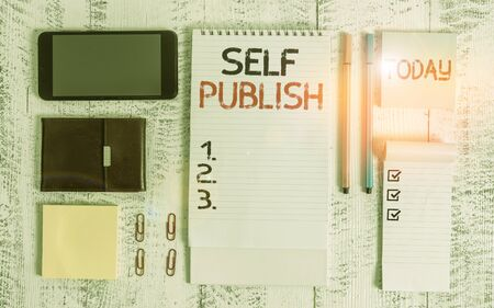 Word writing text Self Publish. Business photo showcasing published their work independently and at their own expense Smartphone wallet sticky notes clips notebook pens note pad wooden table