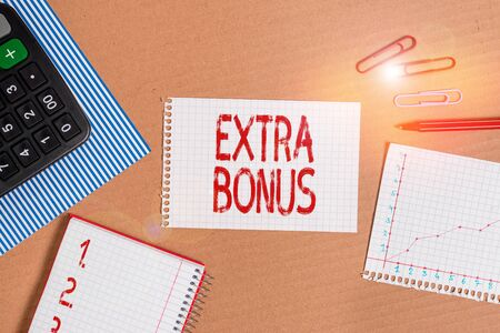 Word writing text Extra Bonus. Business photo showcasing an extra amount of money that is added to someone s is pay Striped paperboard notebook cardboard office study supplies chart paper