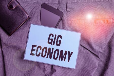 Handwriting text writing Gig Economy. Conceptual photo free market system in which temporary positions are common Smartphone device inside trousers front pocket with wallet and note paper